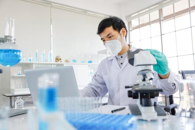 Jonge aziatische mannelijke wetenschapper die aantekeningen maakt terwijl hij door een microscoop kijkt en in een laboratorium zit Premium Foto