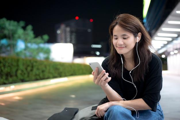 Jonge aziatische meisje, luisteren naar muziek of video-inhoud via de mobiele telefoon Premium Foto