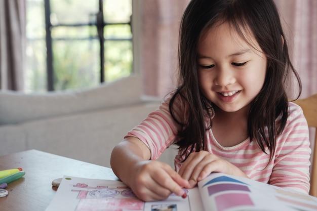 Jonge aziatische meisjestekening thuis, homeschool onderwijs Premium Foto