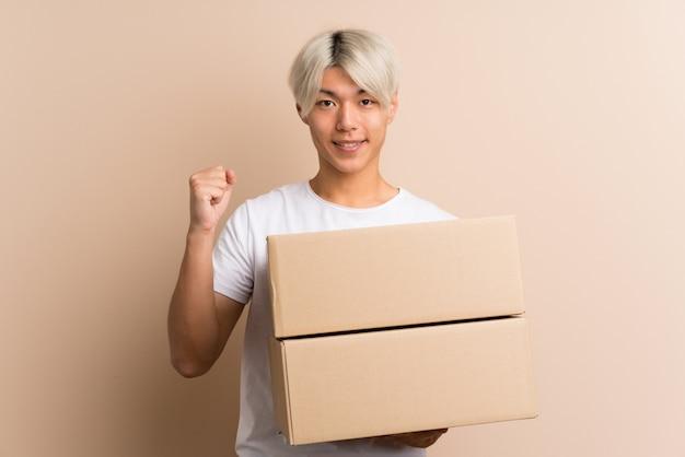 Jonge aziatische mens die een doos houdt om het naar een andere plaats te verplaatsen Premium Foto