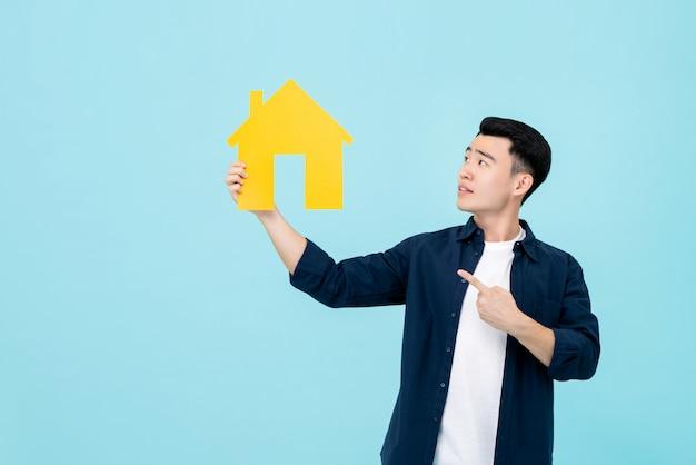 Jonge aziatische mens die en verwijderd huis houdt richt Premium Foto