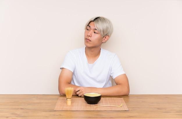 Jonge aziatische mens die met matchathee in een lijst kant kijken Premium Foto