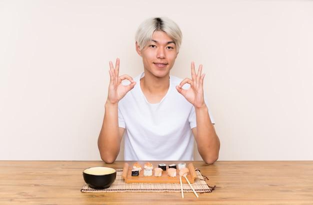 Jonge aziatische mens met sushi in een lijst die een ok teken met vingers toont Premium Foto