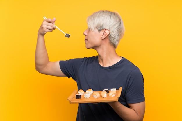 Jonge aziatische mens met sushi over geïsoleerde geel Premium Foto