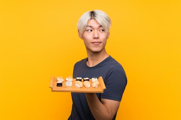 Jonge aziatische mens met sushi over het geïsoleerde gele lachen Premium Foto