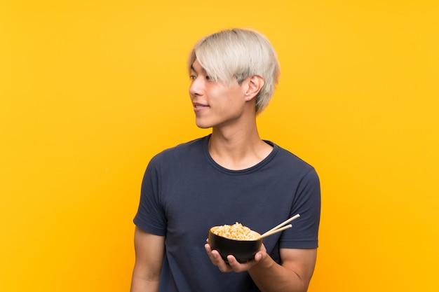 Jonge aziatische mens over geïsoleerde gele kijkende kant Premium Foto