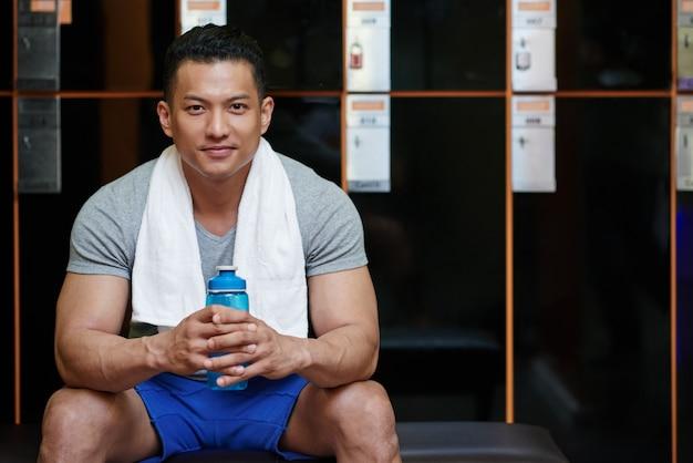 Jonge aziatische mensenzitting in kleedkamer in gymnastiek met waterfles en handdoek Gratis Foto