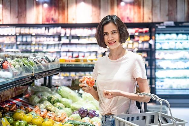Jonge aziatische mooie de kruidenierswinkelmand die van de vrouwenholding in supermarkt lopen, die tomaat op groente en fruitgebied houden met glimlach. Premium Foto