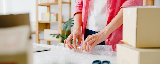 Jonge aziatische ondernemer zakenvrouw verpakking product in kartonnen doos leveren aan klant, thuis kantoor werken. eigenaar van een klein bedrijf, start online marktbezorging, freelance lifestyleconcept. Gratis Foto