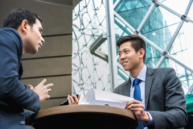 Jonge aziatische partners die werk bespreken Premium Foto