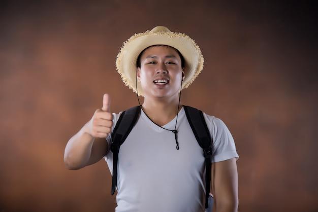 Jonge aziatische reizende backpacker met zak en hoed Gratis Foto