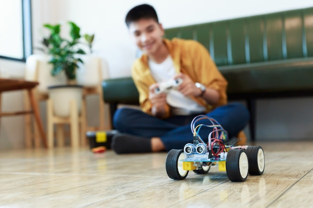 Jonge aziatische tiener die energie en signaalkabel aansluit op sensorchip van speelgoedautowerkplaats. Premium Foto