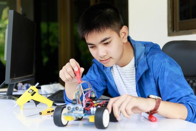 Jonge aziatische tiener geniet met speelgoedautoworkshop. Premium Foto