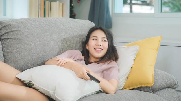 Jonge aziatische tienervrouw die op tv thuis letten, wijfje die het gelukkige liggen voelen op bank in woonkamer. de levensstijlvrouw ontspant thuis in ochtendconcept. Gratis Foto