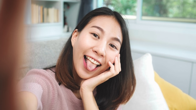 Jonge aziatische tienervrouw vlog thuis, wijfje die smartphone gebruiken die vlogvideo maken aan sociale media in woonkamer. de levensstijlvrouw ontspant thuis in ochtendconcept. Gratis Foto
