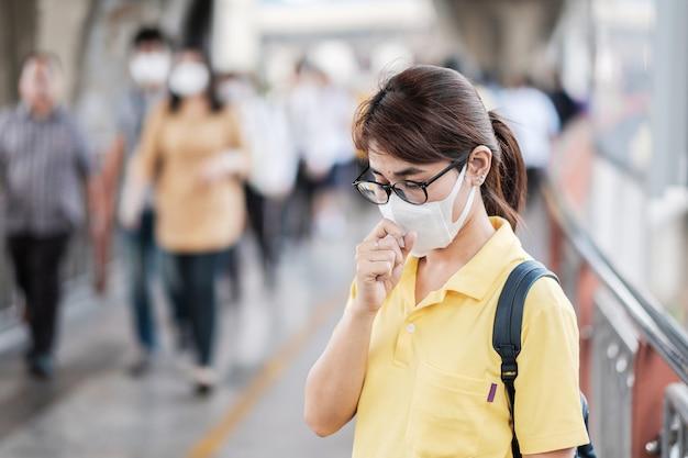 Jonge aziatische vrouw die een beschermingsmasker draagt tegen het nieuwe coronavirus (2019-ncov) of het wuhan-coronavirus op het openbare treinstation, is een besmettelijk virus dat infecties van de luchtwegen veroorzaakt. Premium Foto