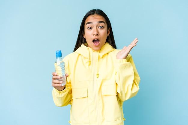 Jonge aziatische vrouw die een fles water houdt die op blauwe muur wordt geïsoleerd verrast en geschokt. Premium Foto