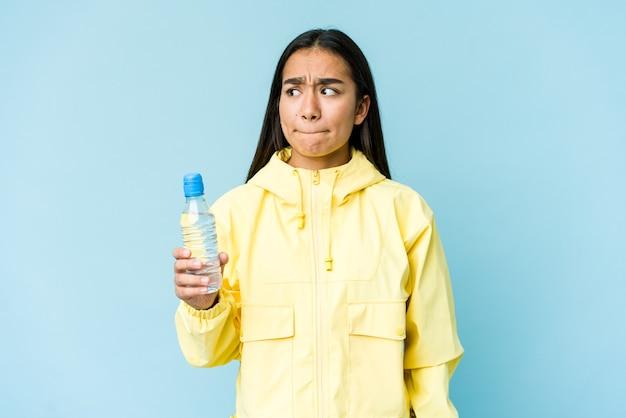 Jonge aziatische vrouw die een fles water houdt die op blauwe muur wordt geïsoleerd verward, voelt twijfelachtig en onzeker. Premium Foto