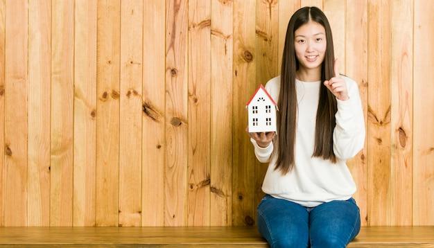 Jonge aziatische vrouw die een huispictogram houdt dat nummer één met vinger toont. Premium Foto