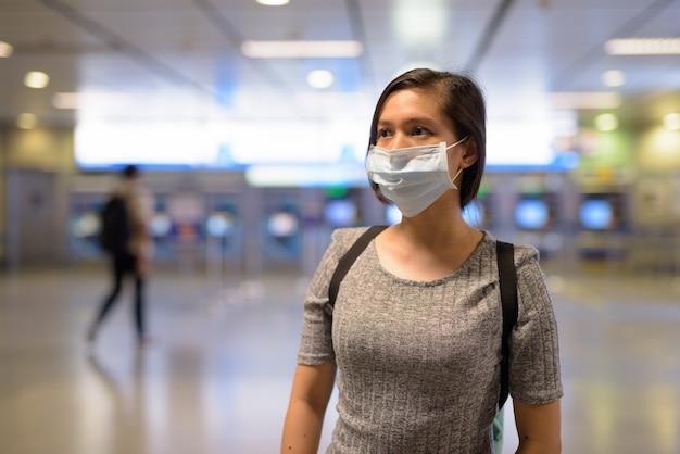 Jonge aziatische vrouw die een masker draagt ter bescherming tegen de uitbraak van het coronavirus op het metrostation Premium Foto