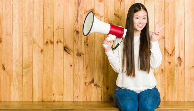 Jonge aziatische vrouw die een megafoon houdt die overwinningsteken toont en breed glimlacht Premium Foto