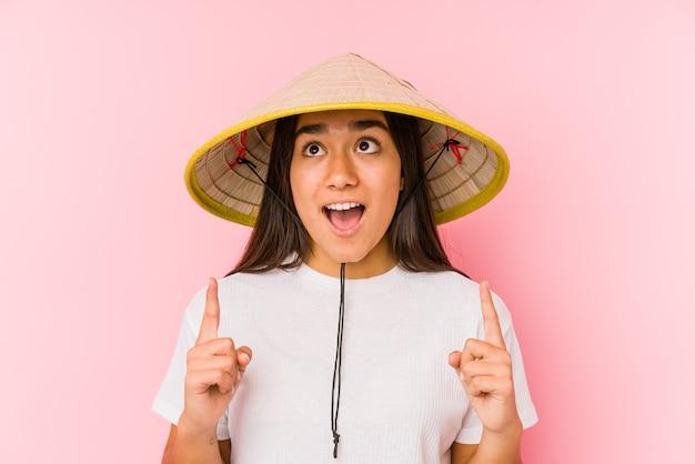 Jonge aziatische vrouw die een vietnamese hoed draagt, geïsoleerd jonge aziatische vrouw die een vietnamese hatpointing upside met geopende mond draagt. Premium Foto