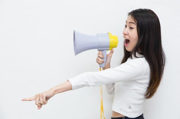 Jonge aziatische vrouw die en met de megafoon op witte achtergrond schreeuwt gilt Premium Foto