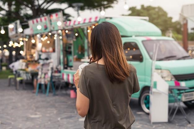 Jonge aziatische vrouw die in de markt van de voedselvrachtwagen loopt Premium Foto