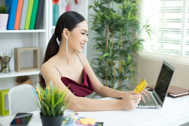 Jonge aziatische vrouw die met creditcard betaalt Gratis Foto
