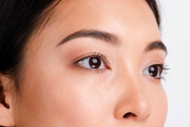 Jonge aziatische vrouw die met duidelijke huid weg kijkt Gratis Foto