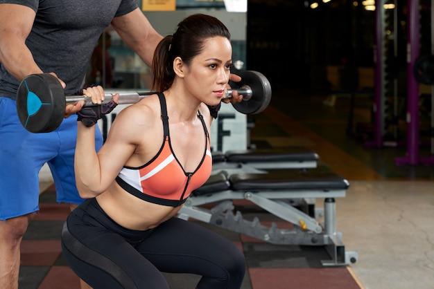Jonge aziatische vrouw die met gewicht uitoefent dat door haar persoonlijke instructeur wordt gesteund Gratis Foto
