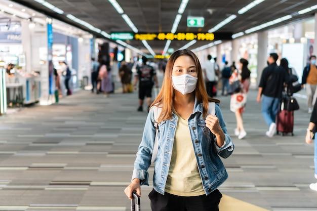 Jonge aziatische vrouw die met gezichtsmasker bij luchthaventerminal loopt. gezondheidszorg en bescherming concept. Premium Foto