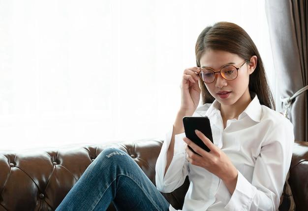 Jonge aziatische vrouw die oogglazen draagt die telefoontekst proberen te lezen. Premium Foto