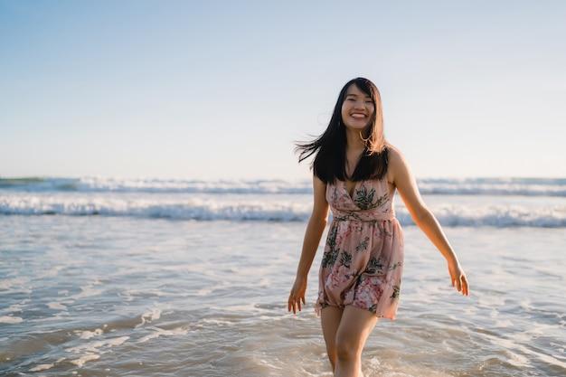 Jonge aziatische vrouw die op strand loopt. mooie vrouwelijke gelukkig ontspant het lopen op strand dichtbij overzees wanneer zonsondergang in avond. Gratis Foto