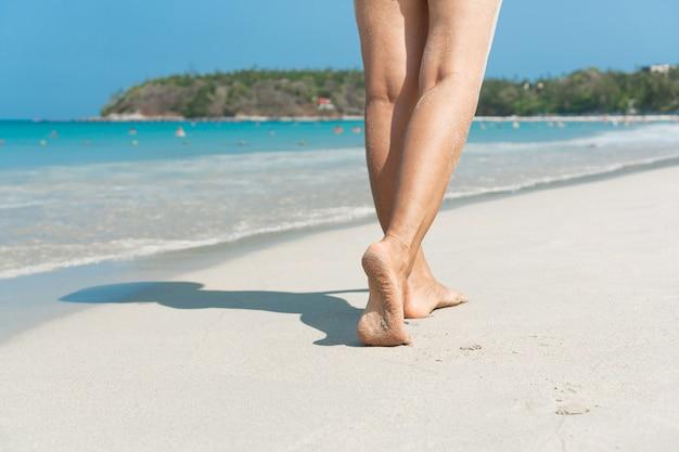 Jonge aziatische vrouw die op zandstrand loopt. reis concept. Premium Foto