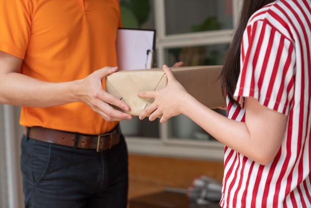Jonge aziatische vrouw die pakketdoos ontvangen van de leveringsmens in oranje eenvormig bij haar thuis. Premium Foto
