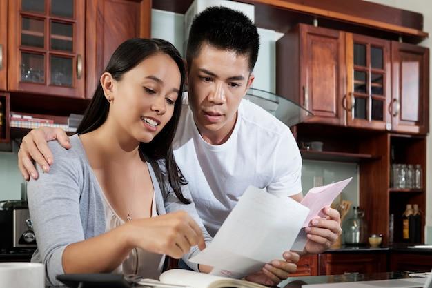 Jonge aziatische vrouw die rekeningen toont aan haar echtgenoot Gratis Foto