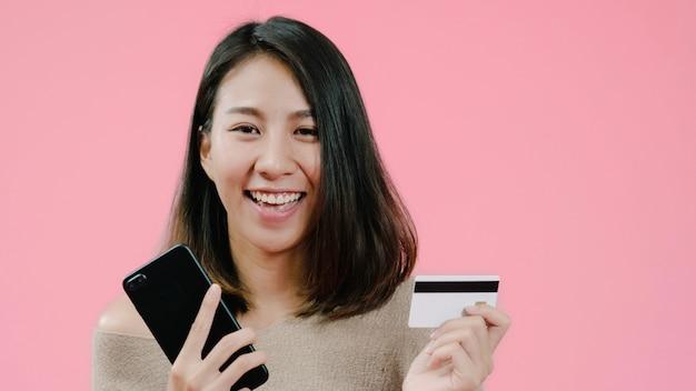 Jonge aziatische vrouw die smartphone gebruiken die online winkelend door creditcard kopen die het gelukkige glimlachen in toevallige kleding over roze achtergrondstudioschot voelen. Gratis Foto