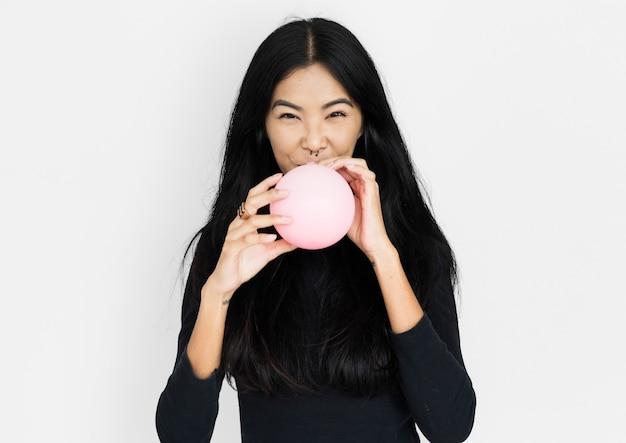 Jonge aziatische vrouw die toevallig een ballon blaast Premium Foto