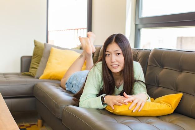 Jonge aziatische vrouw die verbaasd en verward kijkt, lip bijt met een nerveus gebaar, het antwoord op het probleem niet weet Premium Foto