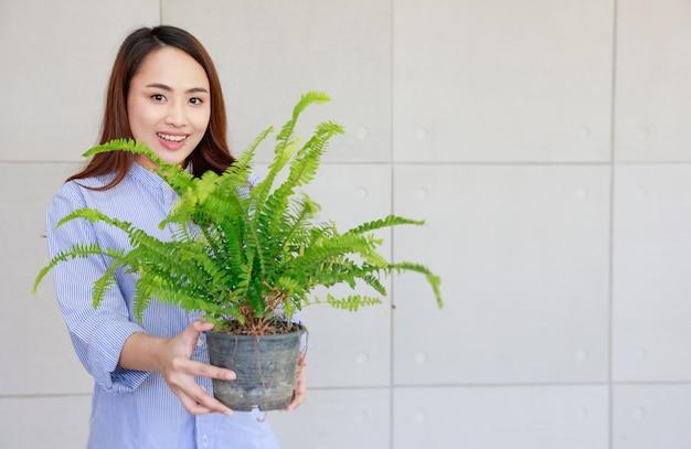 Jonge aziatische vrouw gelukkig lachend en met groene varen in plastic pot te koop tonen. Premium Foto