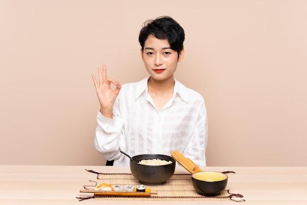 Jonge aziatische vrouw in een lijst met kom van noedels en sushi die een ok teken met vingers tonen Premium Foto