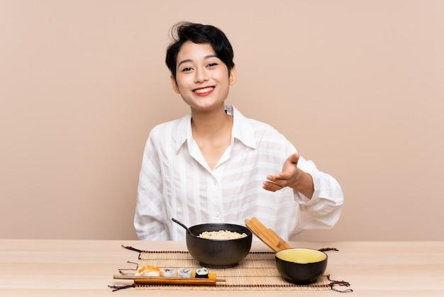 Jonge aziatische vrouw in een lijst met kom van noedels en sushihandenschudden na goede deal Premium Foto