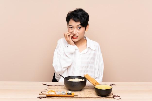 Jonge aziatische vrouw in een tafel met kom noedels en sushi nerveus en bang Premium Foto