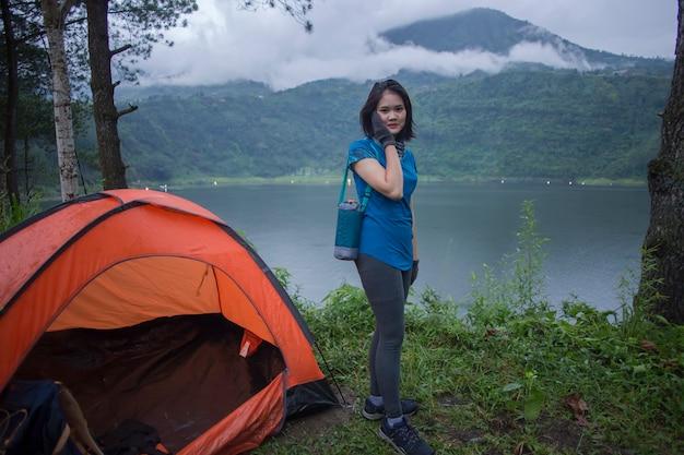 Jonge aziatische vrouw kamperen of picknick in bosmeer. Premium Foto