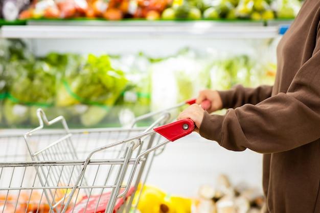 Jonge aziatische vrouw met beschermend masker duwen winkelwagentje voor het kopen van verse groenten in de supermarkt tijdens de uitbraak van het virus covid-19. concept ter preventie van covid-19 virus. Premium Foto