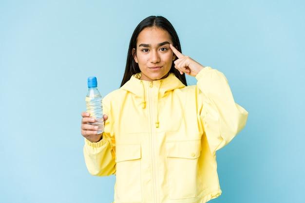 Jonge aziatische vrouw met een fles water geïsoleerd op blauwe muur wijzende tempel met vinger, denken, gericht op een taak. Premium Foto