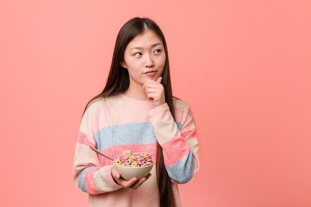Jonge aziatische vrouw met een graangewassenkom die zijdelings met twijfelachtige en sceptische uitdrukking kijkt. Premium Foto