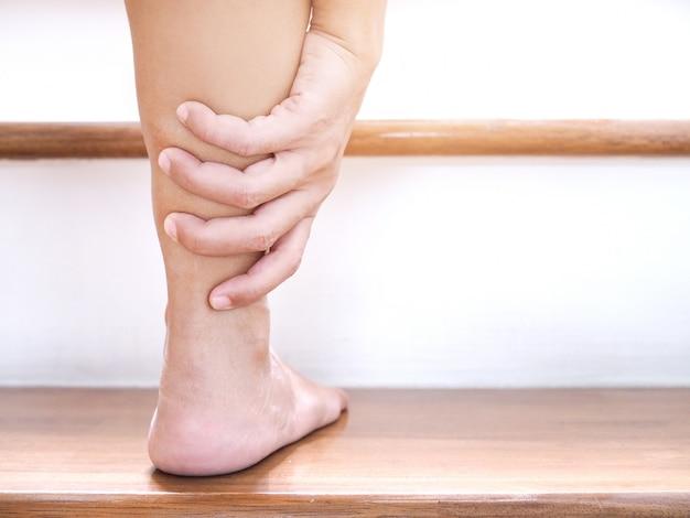 Jonge aziatische vrouw met enkelpijn en acuut beenletsel bij het lopen van trappen. Premium Foto