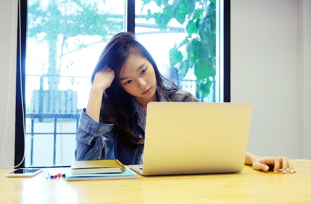 Jonge aziatische vrouw met gefrustreerde uitdrukking terwijl het werken met laptop computer Premium Foto